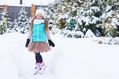 Niña adorable que patina en día de la nieve del invierno Foto de archivo
