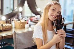 Niña adorable que presenta con el sistema de cepillos del maquillaje Fotografía de archivo