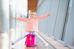 Niña adorable que se divierte en la sentada del aeropuerto fotos de archivo