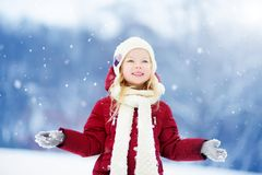Niña adorable que se divierte en parque hermoso del invierno Niño lindo que juega en una nieve fotos de archivo libres de regalías