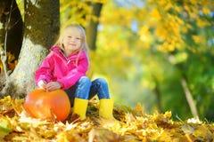 Niña adorable que se divierte en un remiendo de la calabaza en día hermoso del otoño foto de archivo