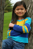 Niña adorable que se inclina para arriba contra árbol Foto de archivo libre de regalías