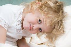 Niña adorable que se reclina en la cama Imágenes de archivo libres de regalías