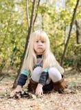 Niña adorable que se sienta en Forest Ground Fotos de archivo