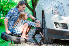 Niña adorable que se sienta en un neumático y un padre de ayuda para cambiar una rueda de coche al aire libre en día de verano he Foto de archivo libre de regalías