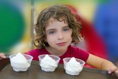 Niña adorable que sostiene el helado tres Imagen de archivo
