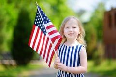 Niña adorable que sostiene la bandera americana al aire libre en día de verano hermoso Imágenes de archivo libres de regalías