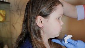 Niña adorable que tiene proceso piercing del oído con el equipo especial en centro de la belleza del trabajador médico metrajes