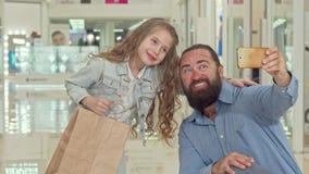 Niña adorable que toma selfies con su padre en el centro comercial metrajes