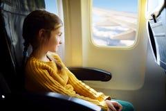 Niña adorable que viaja por un aeroplano Imágenes de archivo libres de regalías