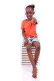 Niña afroamericana negra linda asentada en una pila de abucheo Foto de archivo