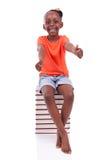 Niña afroamericana negra linda asentada en una pila de abucheo Imagen de archivo