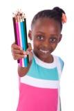 Niña afroamericana negra linda que sostiene el lápiz del color - A Imagen de archivo