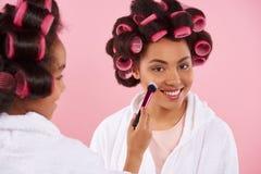 Niña afroamericana que hace maquillaje con la mamá foto de archivo