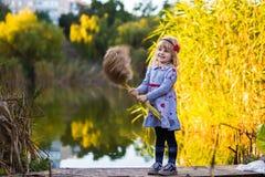 Niña alegre cerca del río con las cañas imagen de archivo