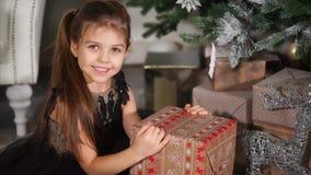 Niña alegre con el regalo de Navidad almacen de metraje de vídeo