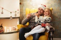 Niña alegre con su papá que sostiene bengalas, mientras que siéntese Imagenes de archivo