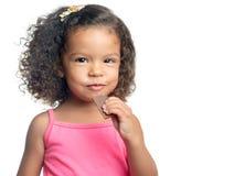 Niña alegre con un peinado afro que come una barra de chocolate Imagenes de archivo