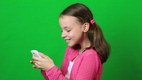 Niña alegre con un smartphone a disposición almacen de video