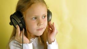 Niña alegre en auriculares en un fondo amarillo Retrato del primer almacen de video