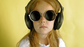 Niña alegre en auriculares en un fondo amarillo Retrato del primer almacen de metraje de vídeo
