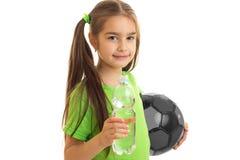 Niña alegre en camisa verde con el balón de fútbol Fotografía de archivo