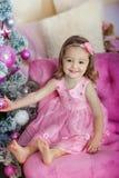 Niña alegre feliz emocionada en la Nochebuena, sentándose debajo de árbol iluminado adornado Tarjeta o cubierta de felicitación Fotografía de archivo libre de regalías