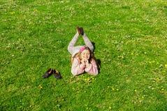 Niña alegre hermosa que miente en hierba verde de la primavera en parque en día magnífico soleado Foto de archivo