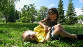 Niña alegre que juega con el pequeño hermano que se divierte junto en la hierba en el día soleado almacen de metraje de vídeo