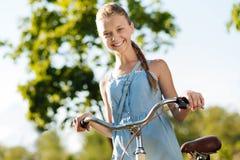 Niña alegre que sostiene su bicicleta Imagenes de archivo