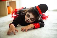 Niña asiática del retrato en el traje de Halloween que actúa asustadiza y fotografía de archivo