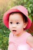 Niña asiática en el sombrero y el vestido rosados foto de archivo libre de regalías