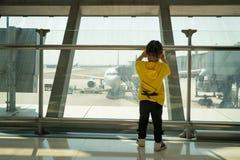Niña asiática en el terminal del embarque del aeropuerto que mira hacia fuera la ventana el aeroplano fotografía de archivo