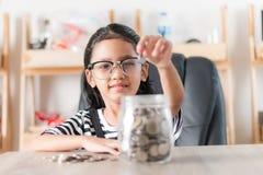 Niña asiática en introducir la moneda al tarro de cristal para el ahorro lunes fotos de archivo libres de regalías