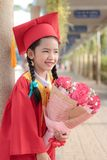 Niña asiática en sonrisa del vestido del ` s del graduado del rojo con felicidad Imágenes de archivo libres de regalías