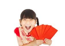 Niña asiática feliz que muestra el sobre rojo Fotografía de archivo