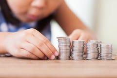 Niña asiática linda que juega con las monedas que hacen pilas del dinero imagen de archivo libre de regalías