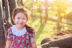 Niña asiática linda que sonríe en jardín Fotos de archivo