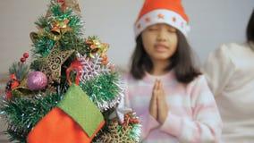 Niña asiática que adorna un árbol de navidad y que ruega para la mejor cosa metrajes