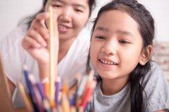 Niña asiática que escoge un lápiz del color oro fotos de archivo