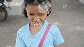 Niña asiática que juega el globo de la burbuja con felicidad metrajes