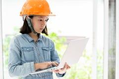 Ni?a asi?tica que lleva el casco de seguridad o el casco anaranjado como sue?o del ingeniero del arquitecto al ni?o futuro, lindo fotografía de archivo