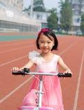 Niña asiática que monta una bicicleta Fotos de archivo libres de regalías