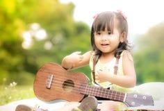 Niña asiática que se sienta en hierba y el ukelele del juego en jardín fotos de archivo libres de regalías
