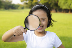 Niña asiática que sostiene una lupa Fotos de archivo