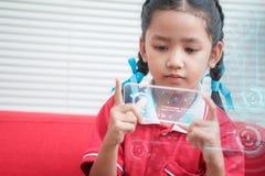 Niña asiática que usa el teléfono elegante móvil con la cabeza de HUD encima del disp Imagenes de archivo