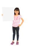 Niña asiática sonriente que lleva a cabo la muestra en blanco Imagen de archivo libre de regalías