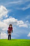 Niña asiática sonriente que se coloca en hierba verde Imagen de archivo libre de regalías