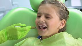 Niña asustada del chequeo dental con el espejo de boca, miedo infantil, tensión almacen de video