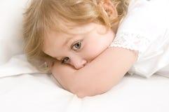 Niña asustada en el primer de la cama Fotografía de archivo libre de regalías